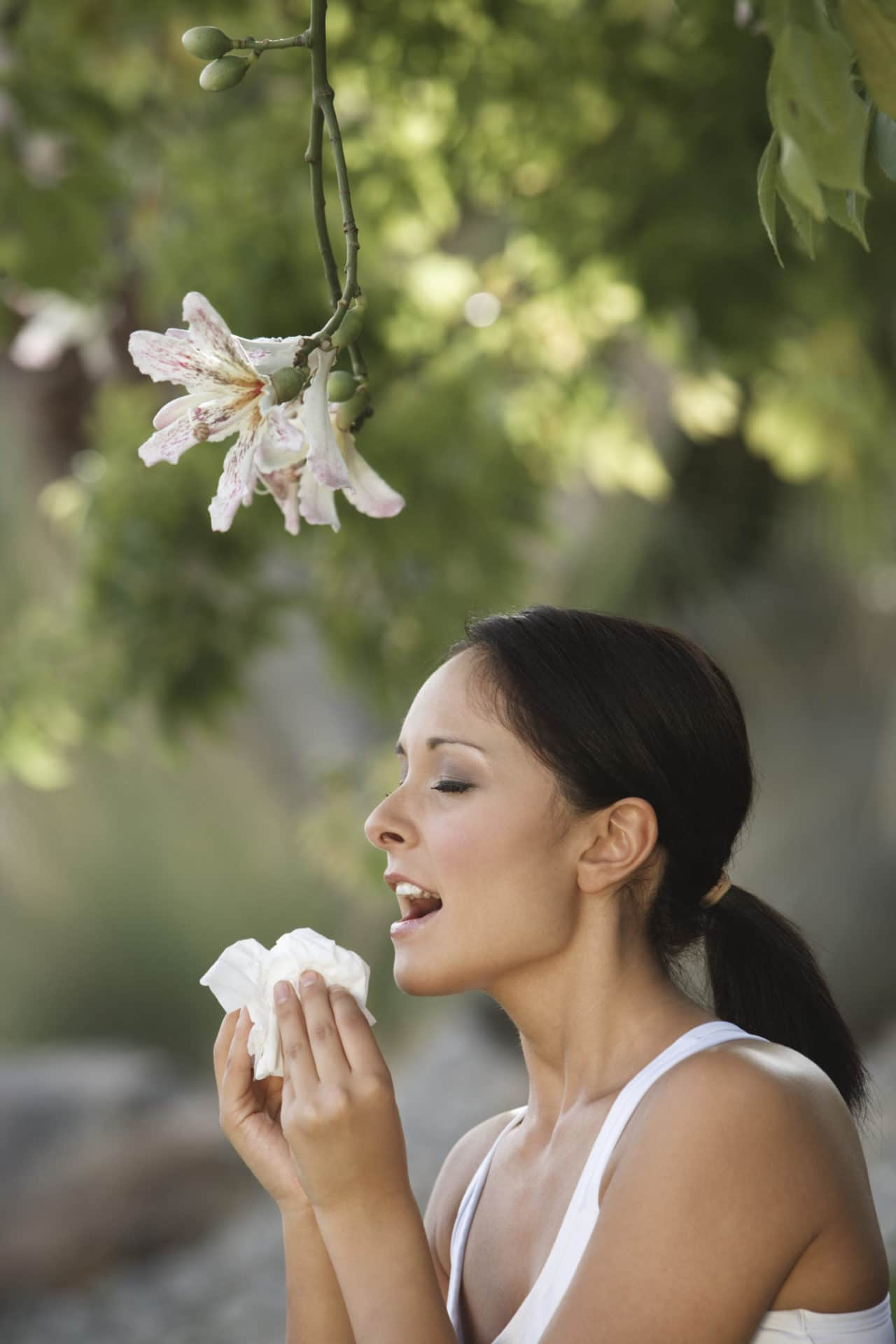 Photo of a person standing under a flowering tree and about to sneeze into a tissue