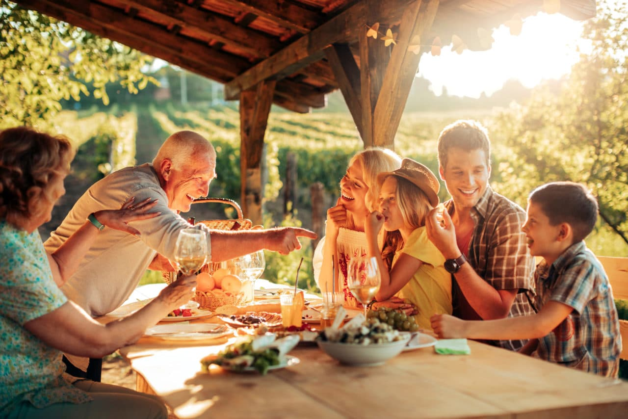 Photo of a multigenerational family gathered around an outdoor dinner table in the evening
