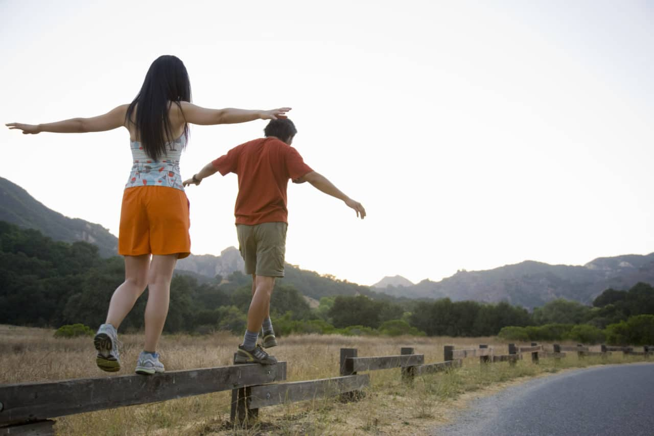 Photo of two people walking on top of a rail fence like a tightrope