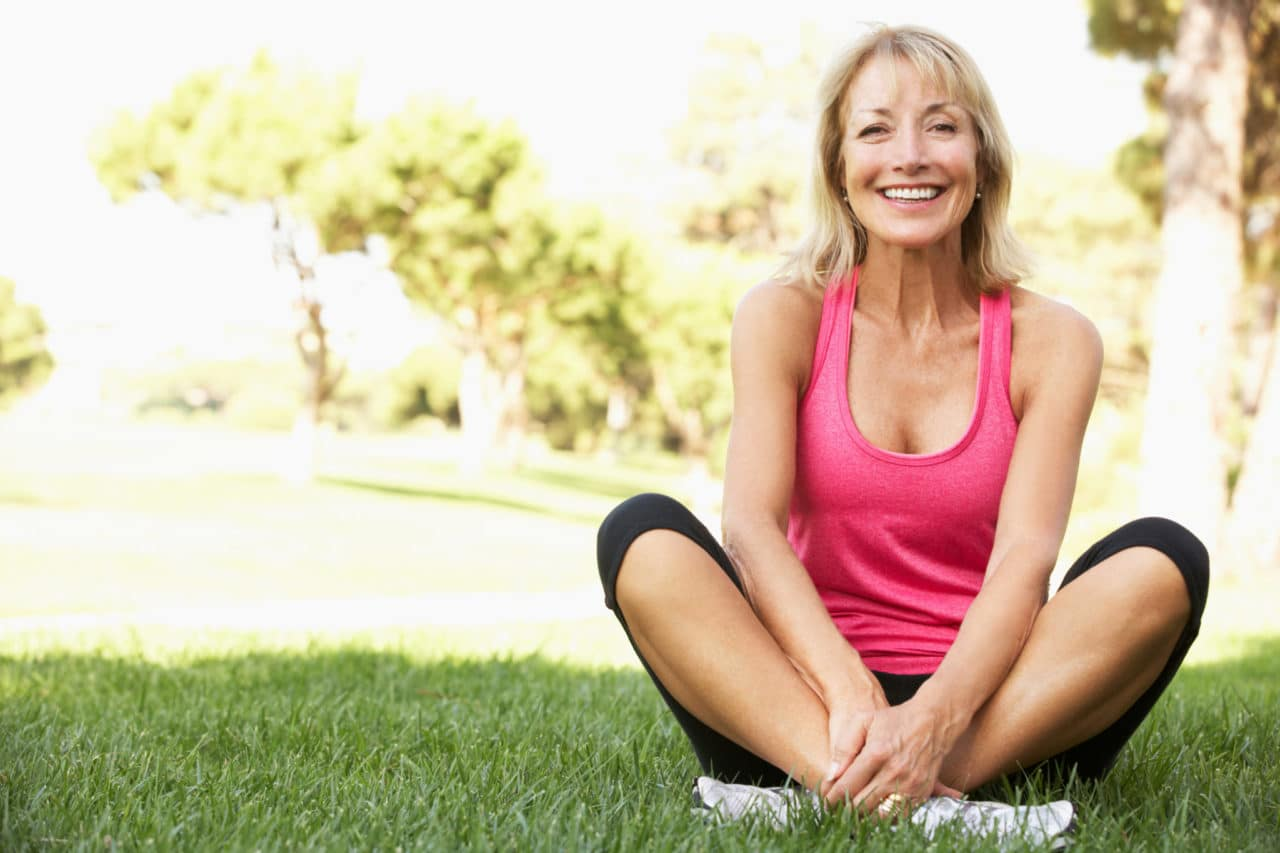 Photo of a smiling person in work-out gear sitting cross-legged on the grass