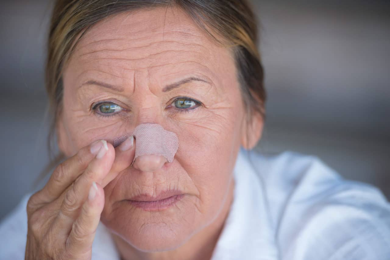Photo of a person lightly touching a bandage on their nose