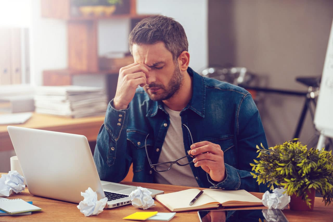 Photo of a person sitting at a desk and pinching the bridge of their nose in pain