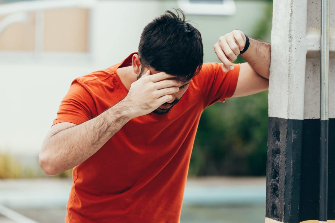 Photo of a person leaning against a wall for support and holding their head