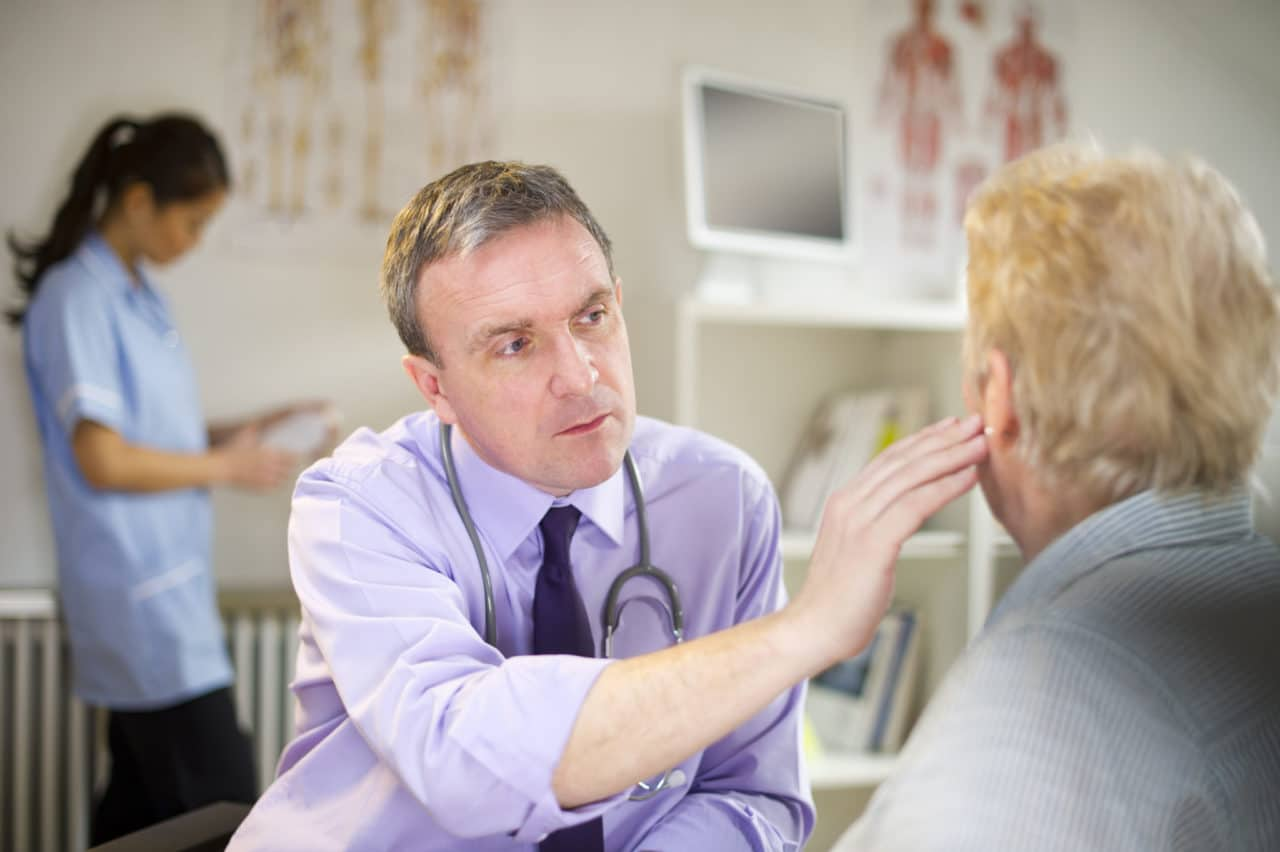 Photo of a provider reaching out and touching the ear of a patient