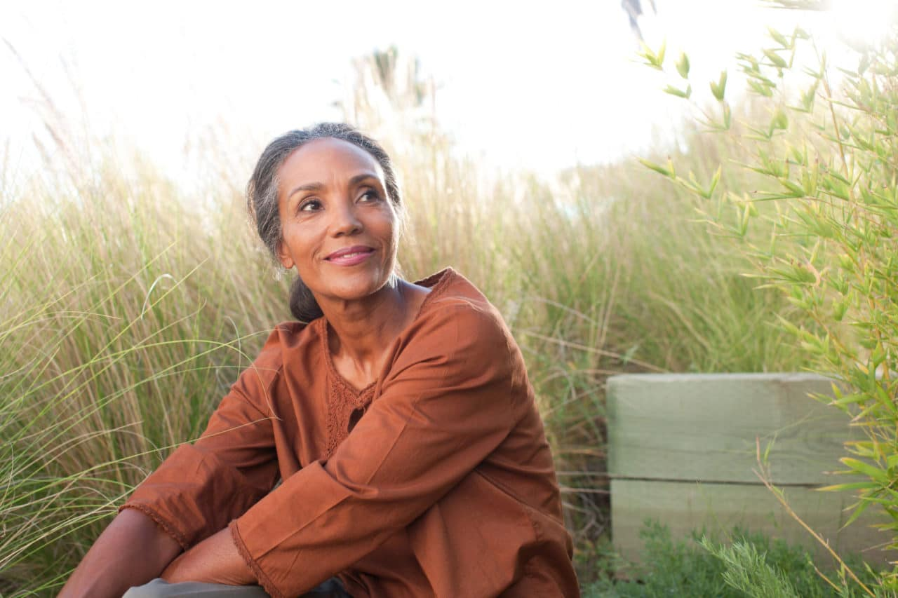 Photo of a person looking peaceful and  sitting in a field of tall grasses