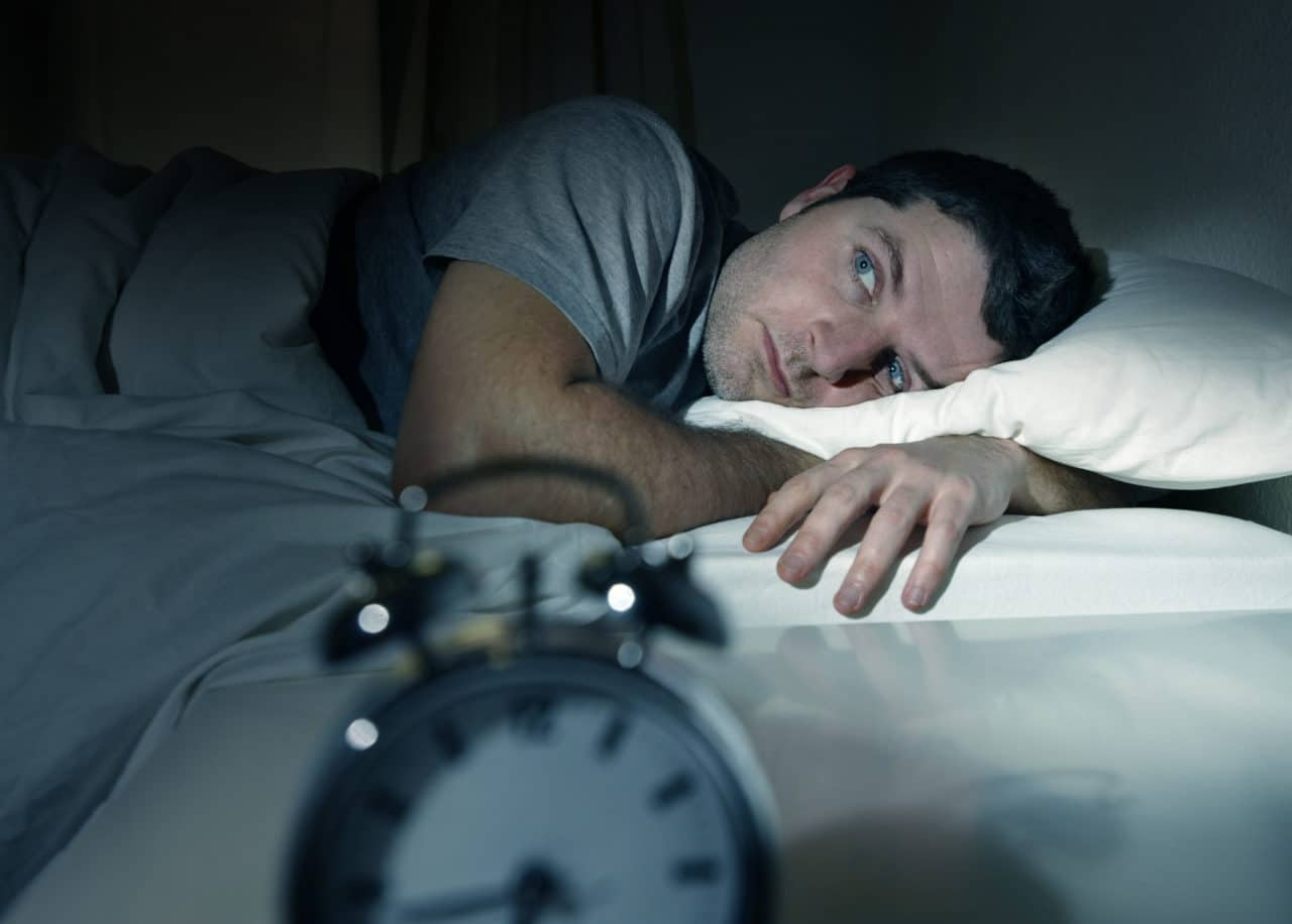 A person laying in bed with eyes wide open as if unable to sleep