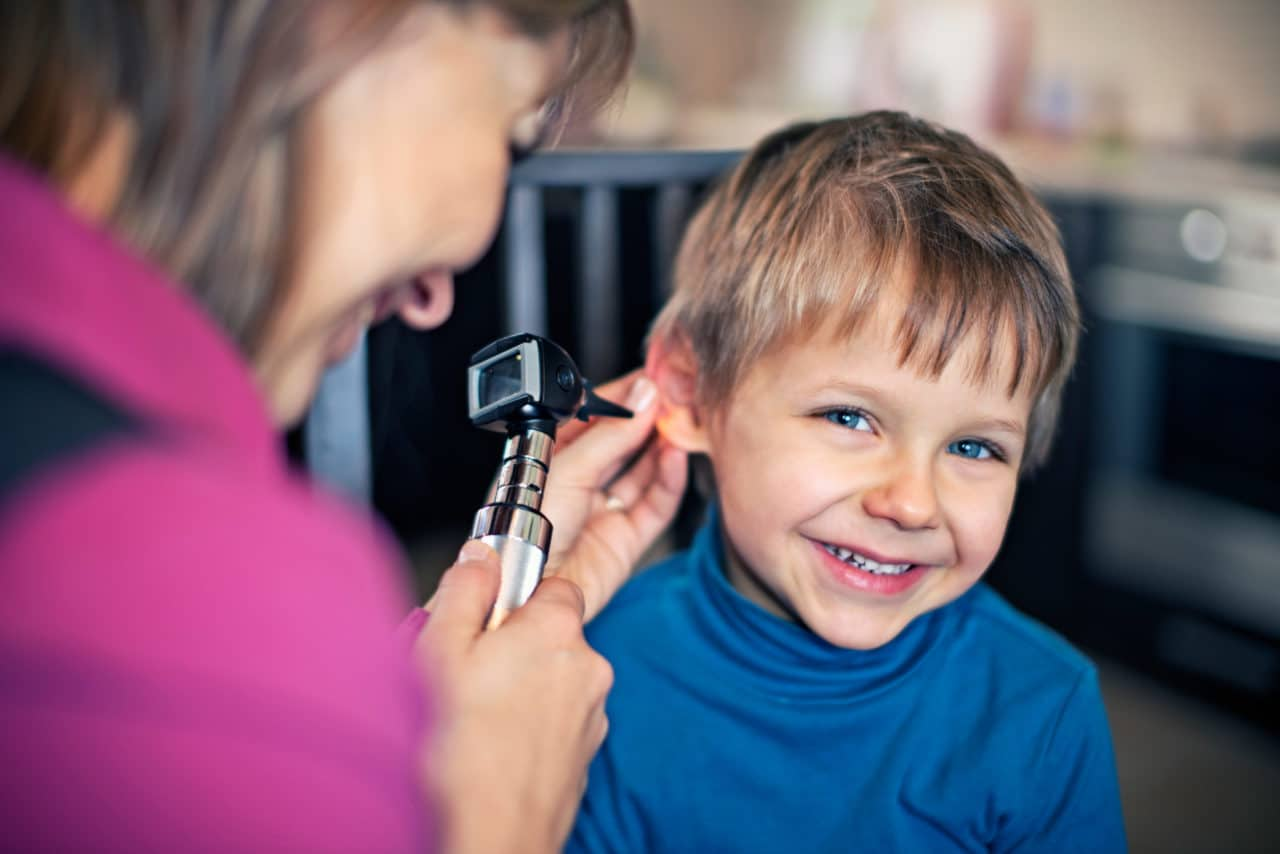 Child smiling as an audiologist holds an otoscope to their ear