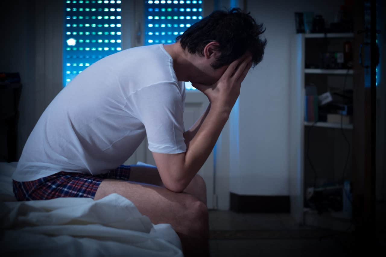 Photo of a person sitting on the edge of their bed, holding their head in their hands