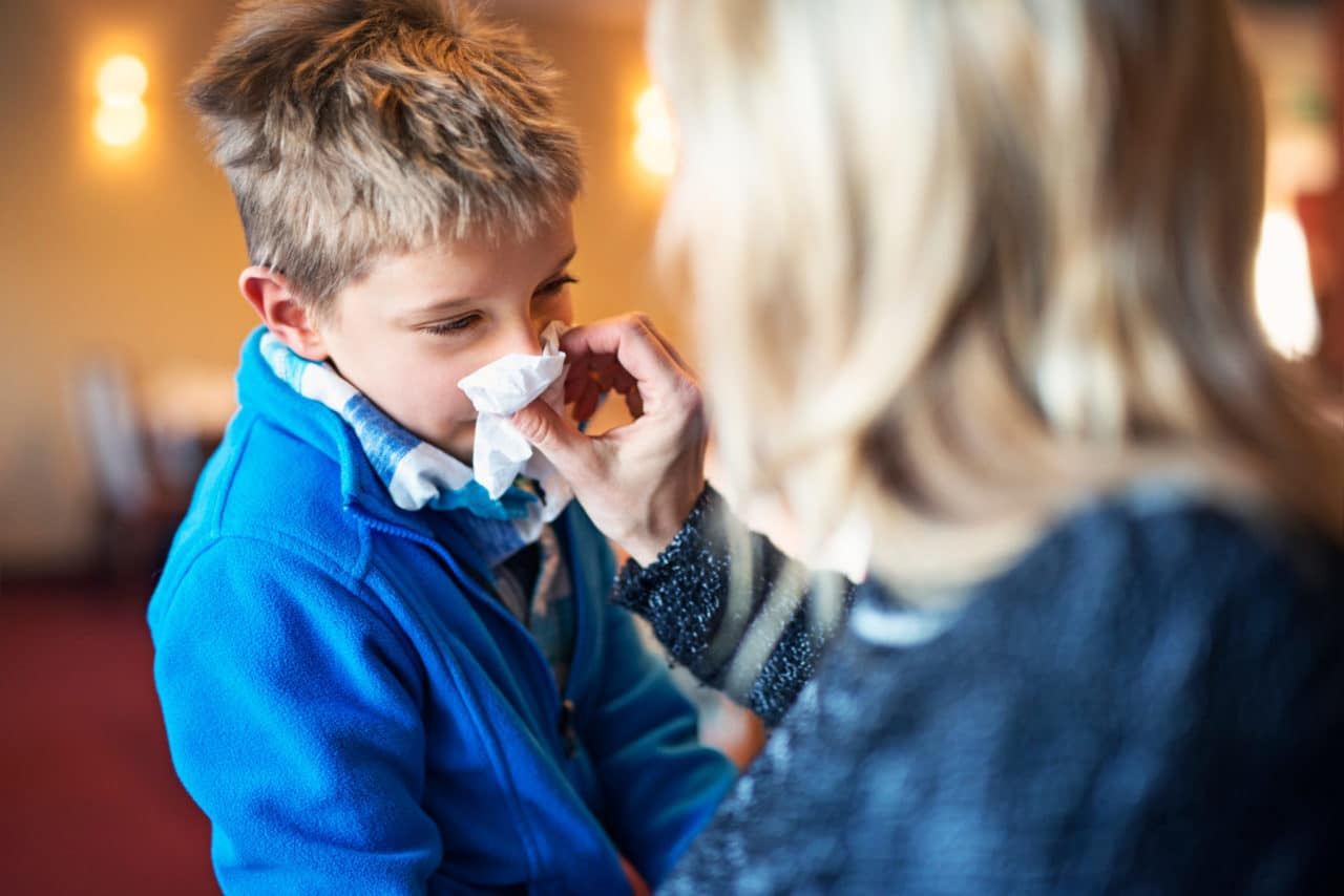 Photo of a child having their nose wiped by an adult