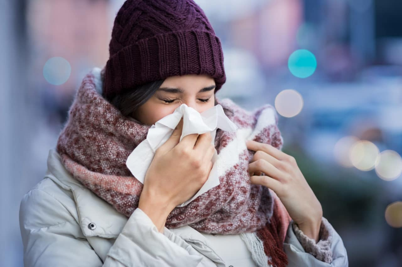 A person wearing a coat, scarf, and hat blowing their nose into a tissue