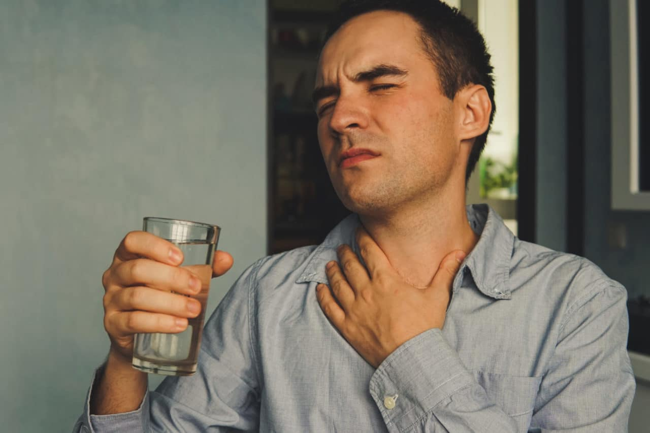 A person holding their throat and wincing in pain while holding a glass of water