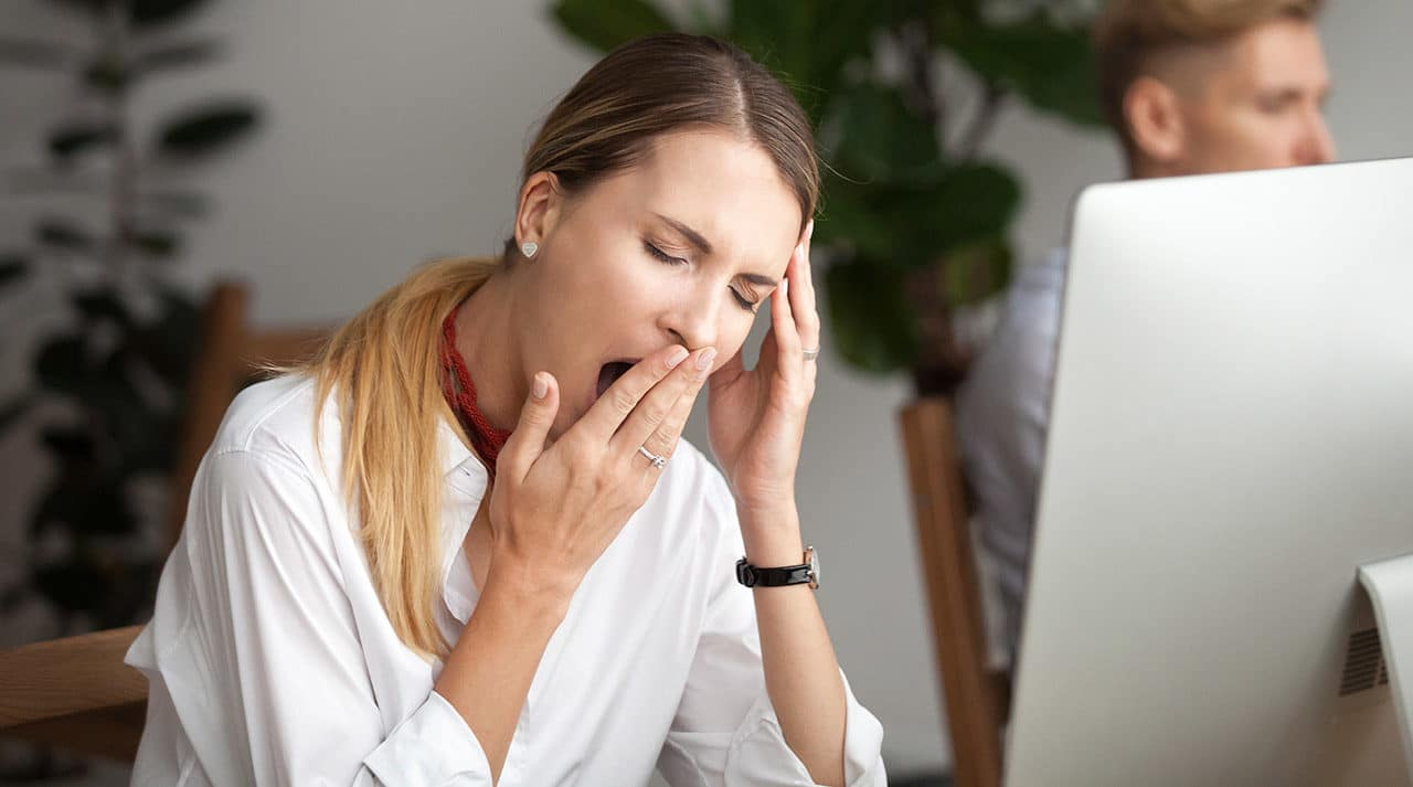 Photo of a person sitting at a desk and covering a yawn