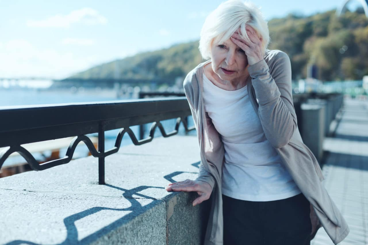 Photo of a person standing on a bridge, leaning against the support and clutching their head in pain