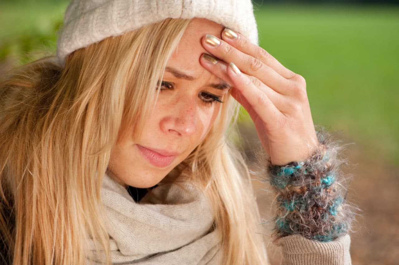 Photo of a person wearing a hat, sweater and scarf holding their forehead and looking worried