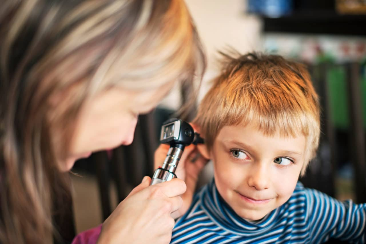 A child smiling up at the audiologist holding an otoscope to their ear