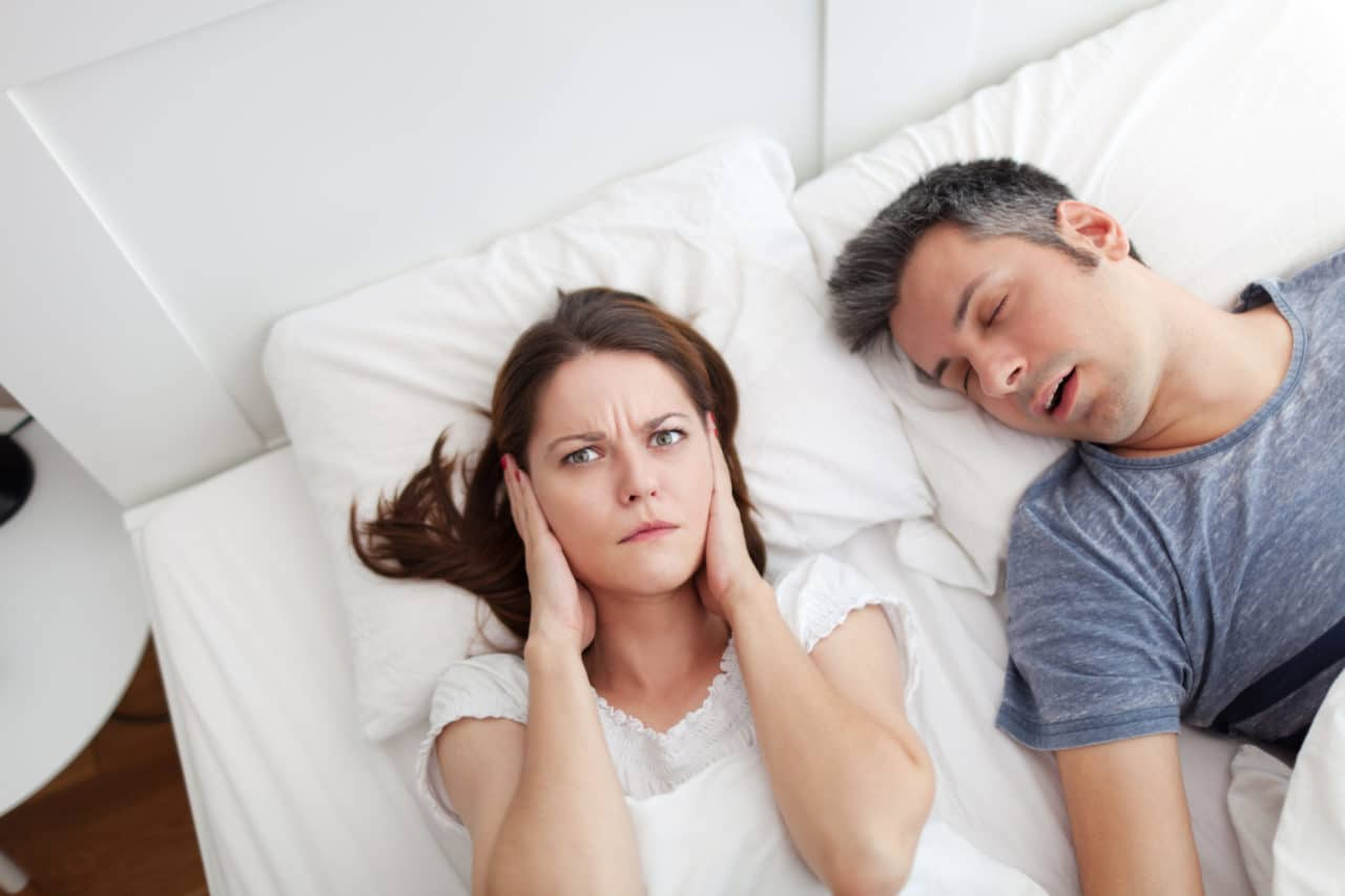 A person looking annoyed and holding their hands over their ears while the other person in the bed sleeps, presumably snoring