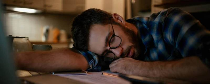 A person who's fallen asleep at their desk
