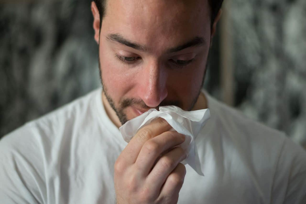 Man with tissue to nose