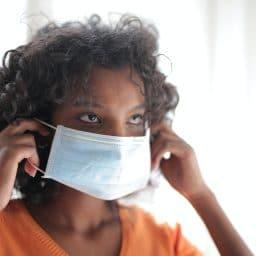 woman putting on basic face mask