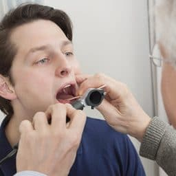 Man getting his throat examined by a doctor