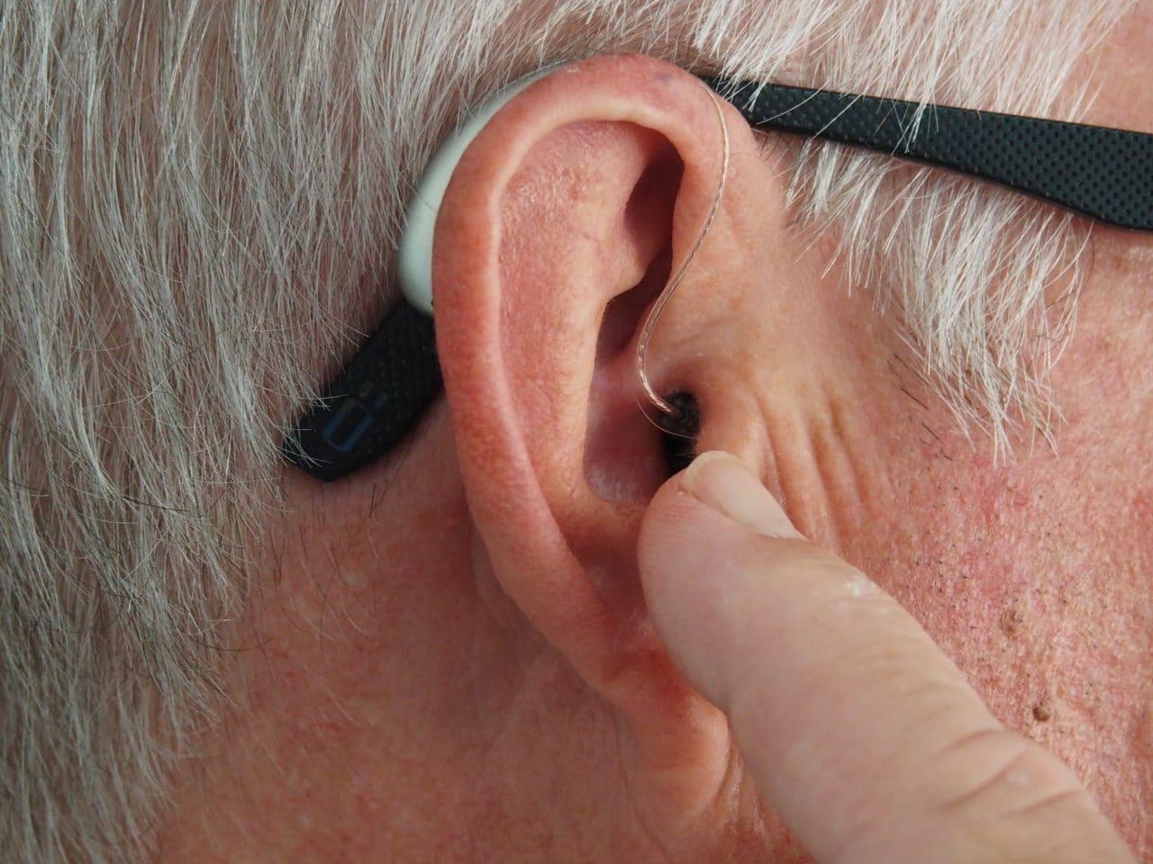 Pan points at his hearing aid.