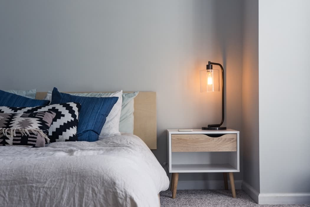Bed and nightstand with lamp.