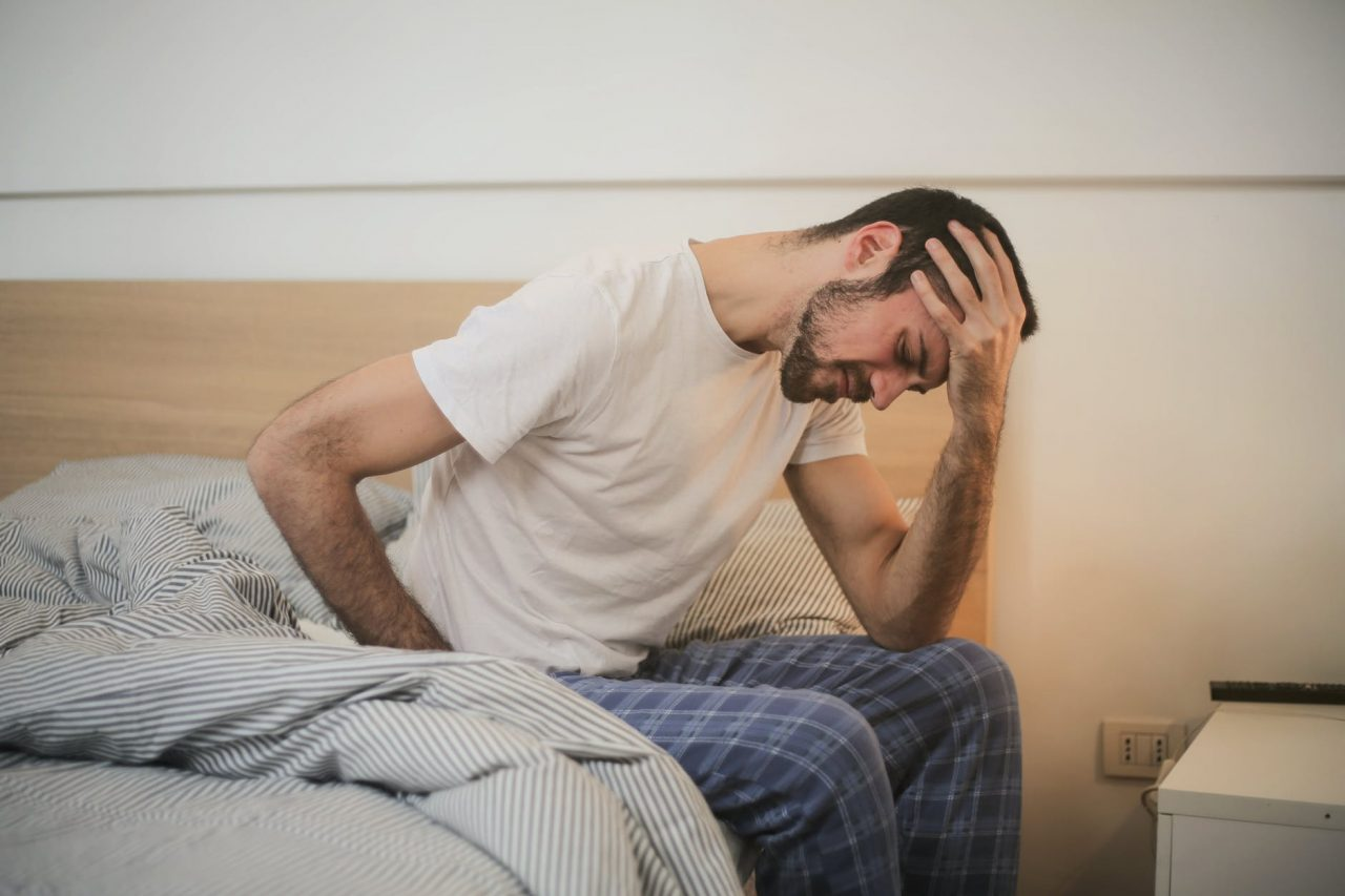 Man sits on edge of bed with headache.