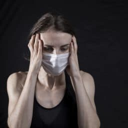 Woman with a headache wearing a mask.