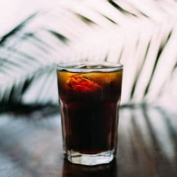 An iced dark beverage in a clear glass.