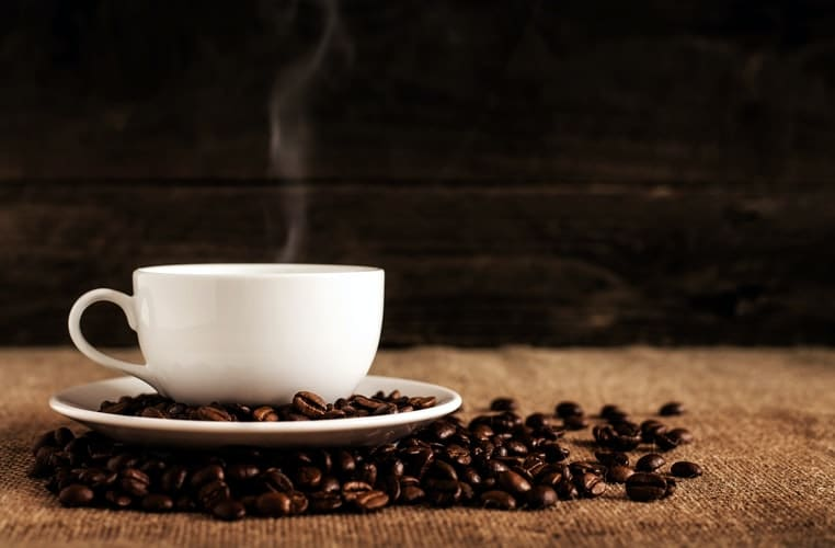 A white cup of coffee surrounded by coffee beans.